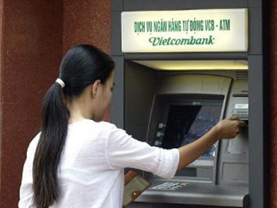 Một công nhân đang rút tiền mặt tại ATM.